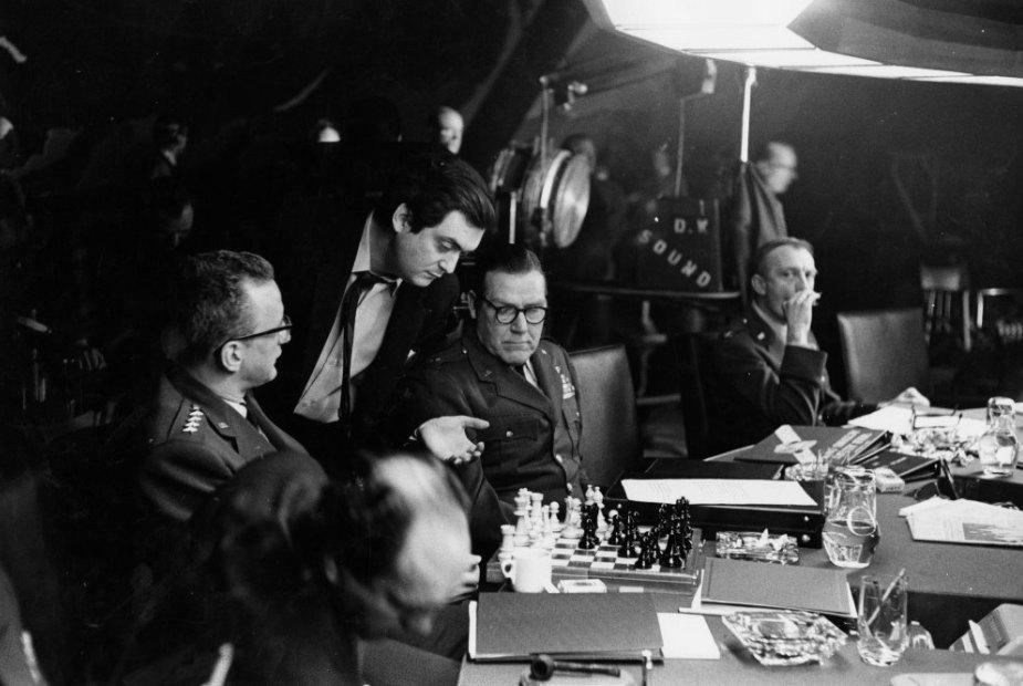 """Stanley Kubrick analiza el tablero ante George C. Scott en la """"sala de la guerra"""""""